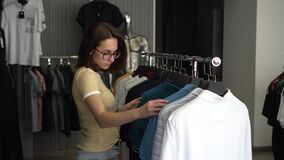 A young woman was choosing a shirt in a store. Clothing store.