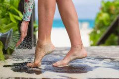 Young woman washes away the sand from her feet on Royalty Free Stock Image