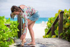 Young woman washes away the sand from her feet on Royalty Free Stock Photos