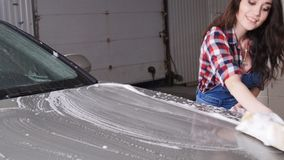 Young woman washes the car with a sponge. Indoors stock video footage