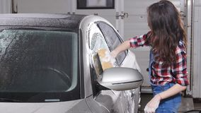 Young woman washes the car with a sponge. Indoors stock video