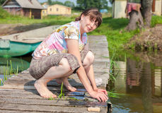 Young woman washes clothes on wooden jetty by the lake in summer Stock Photos