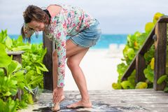 Young woman washes the sand from her feet on white Royalty Free Stock Images