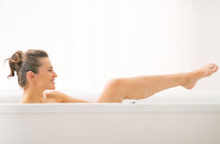 Young woman washing in bathtub Royalty Free Stock Image