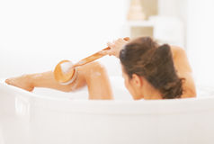 Young woman washing in bathtub. rear view Royalty Free Stock Images