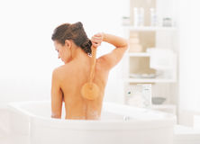 Young woman washing with body brush in bathtub Stock Photos
