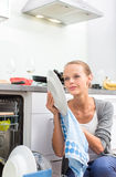 Young woman washing dishes in her modern kitchen Stock Image