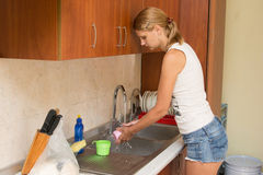 Young woman washing dishes in the kitchen Royalty Free Stock Photo