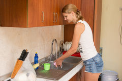 Young woman washing dishes in the kitchen Stock Photo