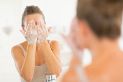 Young woman washing face in bathroom Royalty Free Stock Photography
