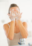 Young woman washing face in bathroom Royalty Free Stock Photo