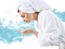 Young woman washing face with clean water. Young woman washing face with clean water in white bathrobe and towel. Morning hygiene concept Stock Images