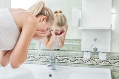 Young woman washing face Royalty Free Stock Images