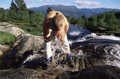 Young woman washing face in river Royalty Free Stock Photography