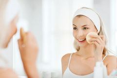 Young woman washing face with sponge at bathroom Stock Photos