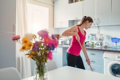 Young woman washing floor with mop in modern kitchen decorated with flowers. Household chores royalty free stock photography