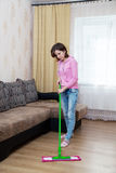 Young woman washing floor with a mop Stock Photography