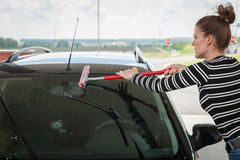 Young woman washing the glass of a car Royalty Free Stock Photos