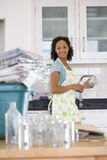 Young woman washing glass jar and can for recycling, smiling (differential focus). Young women washing glass jar and can for recycling, smiling (differential Stock Photo