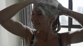 Woman Washing Hair. Young woman washing hair under shower in bathroom with window, 4k shot stock video