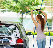 Young woman washing her car Royalty Free Stock Photography