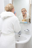 Young woman washing her face in bathroom Royalty Free Stock Images