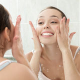 Young woman washing her face with clean water Stock Photo