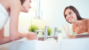 Young woman washing her face with clean water in bathroom Stock Photography