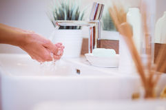 Young woman washing her face with clean water in bathroom Royalty Free Stock Photography