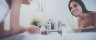 Young woman washing her face with clean water in bathroom Stock Photos