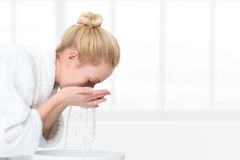 Young woman washing her face Stock Photo