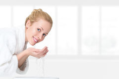 Young woman washing her face Royalty Free Stock Photography