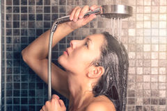 Young woman washing her long hair under the shower Royalty Free Stock Images