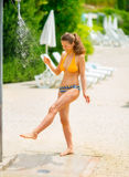 Young woman washing legs under outdoors shower Stock Photos