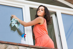 Young woman washing plastic windows in house Royalty Free Stock Photos