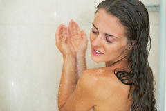 Young woman washing in shower. Young woman with brown hair washing in shower stock photos