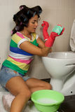 Spring Clean out. Young woman washing toilet in the flat Stock Images
