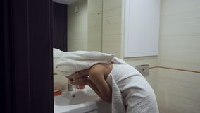 Young woman washing up her face in bathroom. stock footage