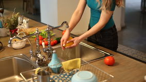 Young woman washing vegetables stock video footage