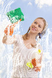 Young woman washing window. Portrait of young female washing window and smiling royalty free stock photo