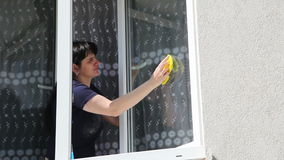 Young woman washing the window stock video