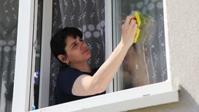 Young woman washing the window stock footage
