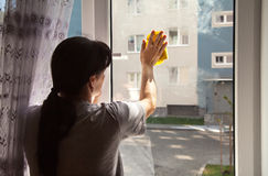 Young woman washing the window Royalty Free Stock Image