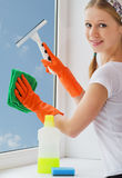 Young woman washing windows. Attractive young woman washing window and smiling stock image
