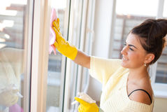 Spring Clean out. Young woman washing windows in the flat Royalty Free Stock Images