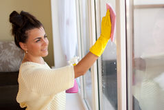 Spring Clean out. Young woman washing windows in the flat Royalty Free Stock Image
