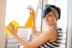 Spring Clean out. Young woman washing windows in the flat Stock Photos