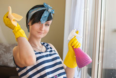 Spring Clean out. Young woman washing windows in the flat Royalty Free Stock Photos