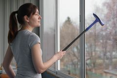 Young woman washing windows with rubber mop royalty free stock image