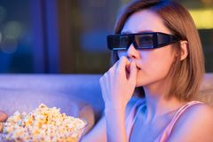 Woman watch 3d horror movies. Young woman watch 3d horror movies with popcorn at night royalty free stock image